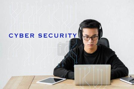 Foto de Hacker asiático que utiliza laptop y se sienta cerca de ilustrar con seguridad cibernética. - Imagen libre de derechos