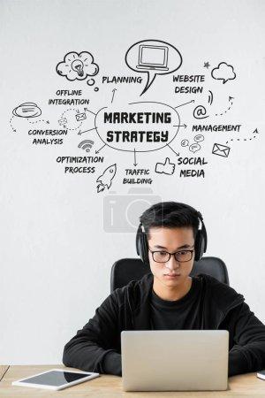 Photo pour Asian seo gestionnaire utilisant ordinateur portable et assis près de l'illustration avec des mots de concept de la stratégie de marketing - image libre de droit