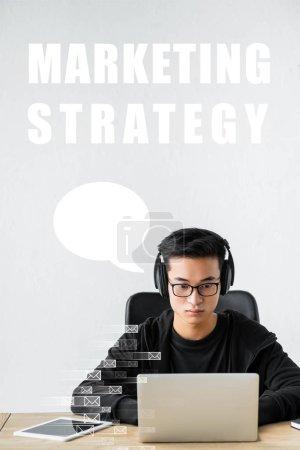 Photo pour Seo manager asian utilisant un ordinateur portable et assis près de l'illustration de la stratégie de marketing - image libre de droit