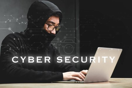Photo for Asian hacker using laptop and sitting near cyber security illustration - Royalty Free Image