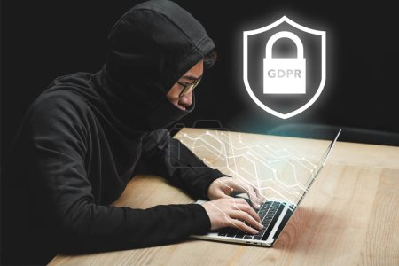 asian hacker using laptop and sitting near padlock illustration and gdpr lettering