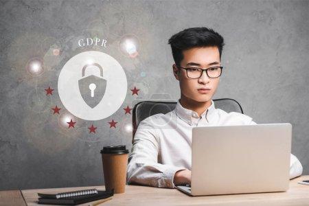 Photo pour Un homme d'affaires asiatique qui utilise un ordinateur portatif et qui est assis près d'une illustration de cadenas et de lettres gdpr - image libre de droit