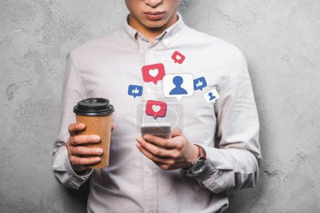 Photo for Cropped view of seo manager holding paper cup, using smartphone with emojis illustration - Royalty Free Image