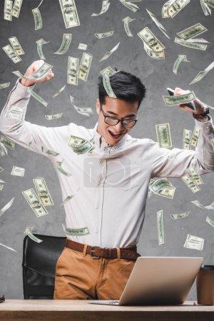 Photo pour Homme d'affaires asiatique heureux montrant un geste positif et l'illustration de billets de banque en dollars - image libre de droit
