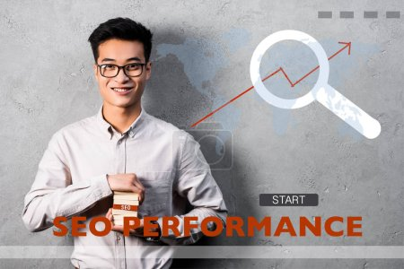 Photo for Smiling asian seo manager holding rectangle with seo lettering and standing near seo performance illustration - Royalty Free Image