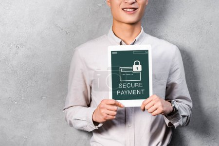 cropped view of smiling businessman holding digital tablet with secure payment illustration