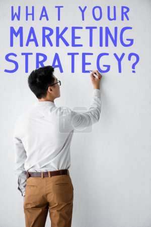 Photo for Back view of seo manager writing on wall with what your marketing strategy illustration - Royalty Free Image