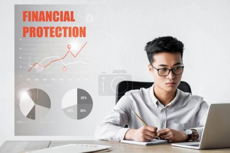 Foto de Asian seo manager using laptop and sitting near illustration with financial protection lettering. - Imagen libre de derechos