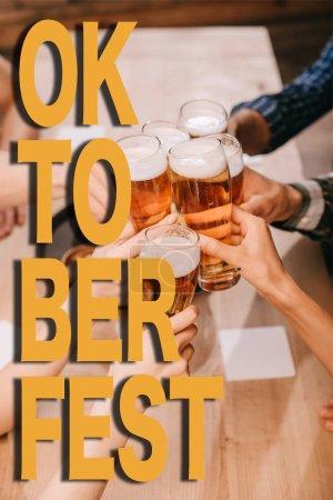 Photo pour Vue croisée d'amis multiculturels lunettes de clairon avec bière au pub avec illustration à la Fête de la bière - image libre de droit