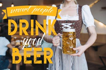 Photo pour Vue partielle d'une serveuse en allemand costume national tenant une tasse de bière légère près de personnes intelligentes boire une bonne illustration de bière - image libre de droit