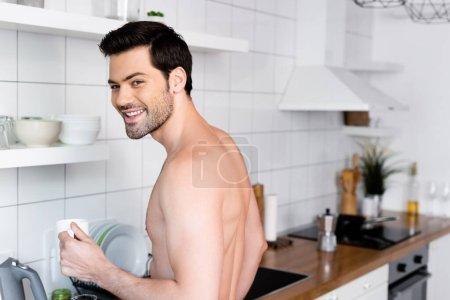sonriente hombre sin camisa sosteniendo taza de café en la cocina por la mañana
