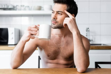 Photo for Thoughtful shirtless man holding cup of coffee on kitchen in morning - Royalty Free Image
