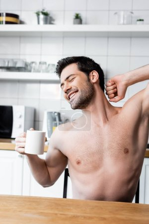 happy shirtless man stretching and holding cup of coffee on kitchen in morning