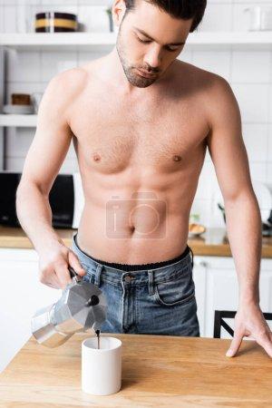 homme musclé torse nu versant le café du pot dans la tasse sur la cuisine