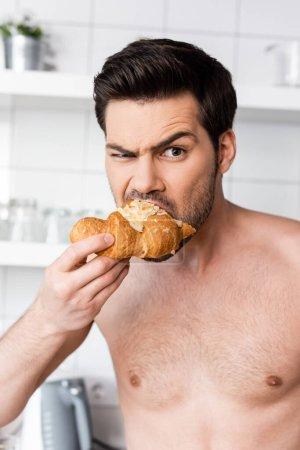 shocked shirtless man eating croissant on kitchen in morning