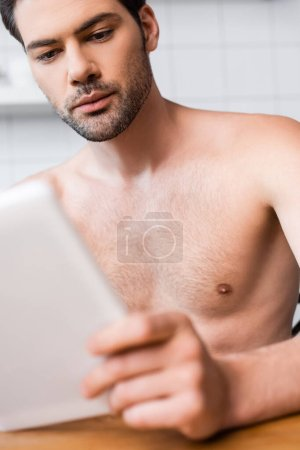 handsome sexy shirtless man using digital tablet, self isolation