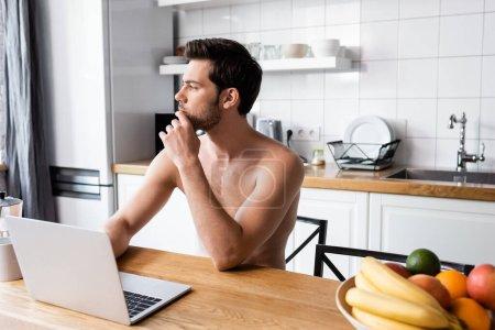 Photo for Pensive shirtless freelancer working on laptop on kitchen - Royalty Free Image