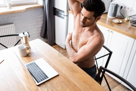 Photo for Sexy shirtless freelancer working on laptop on kitchen with coffee - Royalty Free Image
