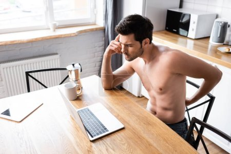 Photo for Thoughtful shirtless freelancer working on laptop on kitchen with coffee - Royalty Free Image