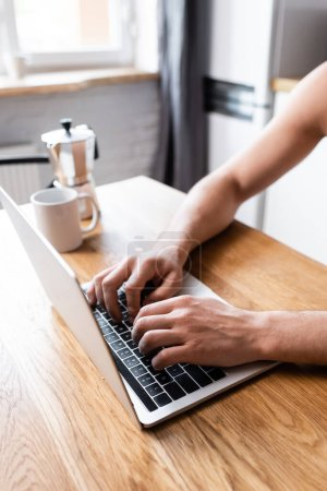 cropped view of male freelancer working on laptop on kitchen with coffee pot and cup