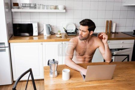 Photo pour Pigiste réfléchi manger de la pomme tout en travaillant sur ordinateur portable sur la cuisine - image libre de droit