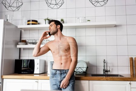 Photo for Young shirtless man talking on cellphone in kitchen at home - Royalty Free Image