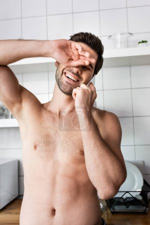 sexy laughing man talking on cellphone in kitchen at home
