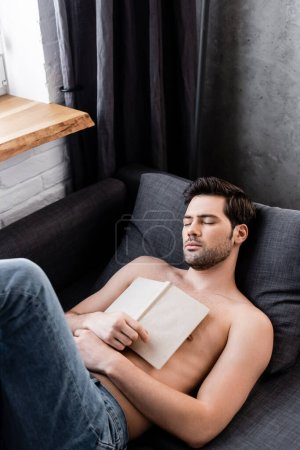 Photo for Sexy shirtless man sleeping with book on sofa - Royalty Free Image