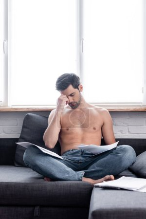 Photo for Worried shirtless freelancer working with documents on sofa during quarantine - Royalty Free Image