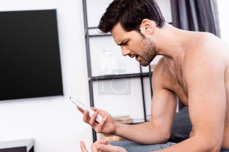 Photo pour Homme torse nu en colère regardant la télécommande du climatiseur à la maison - image libre de droit