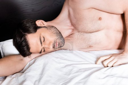 handsome shirtless man sleeping on bed at home
