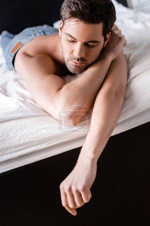 Photo pour Bel homme torse nu couché sur le lit à la maison - image libre de droit