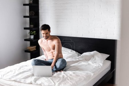 Photo for Happy shirtless man networking on laptop in bed - Royalty Free Image
