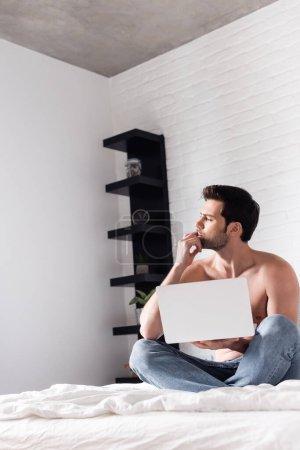 Photo pour Travailleur indépendant masculin torse nu réfléchi travaillant sur ordinateur portable au lit - image libre de droit