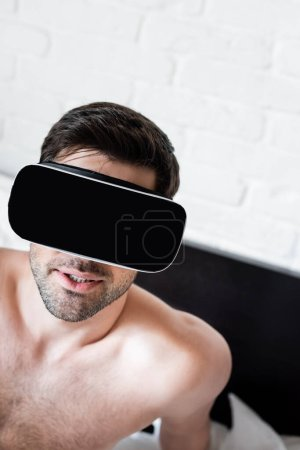handsome shirtless man using virtual reality headset on bed