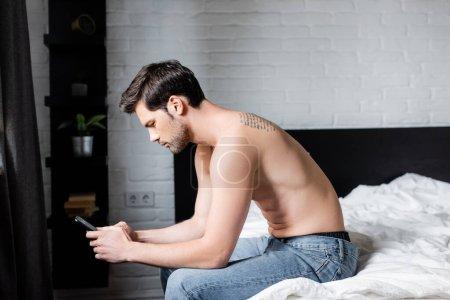 Photo pour Jeune homme torse nu utilisant smartphone sur le lit - image libre de droit