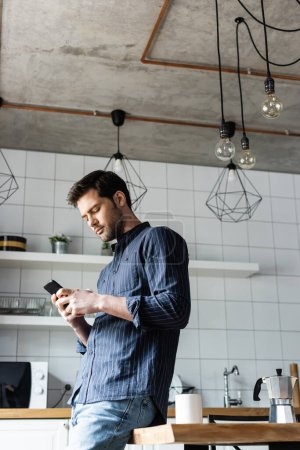 Photo pour Jeune homme utilisant un smartphone sur la cuisine avec du café pendant la quarantaine - image libre de droit