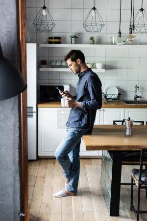 Photo pour Bel homme tenant une tasse de café tout en utilisant smartphone sur la cuisine pendant la quarantaine - image libre de droit