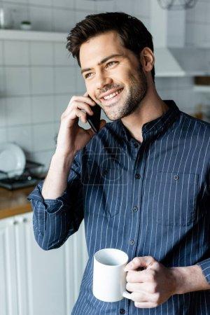 Photo pour Gai bel homme tenant tasse de café tout en parlant au téléphone sur la cuisine pendant la quarantaine - image libre de droit