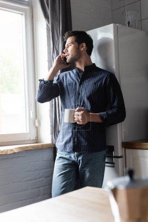 Photo pour Bel homme tenant une tasse de café tout en parlant sur téléphone portable sur la cuisine pendant la quarantaine - image libre de droit