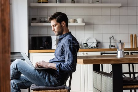 Photo for Handsome freelancer working laptop with blank screen on kitchen with coffee pot during self isolation - Royalty Free Image