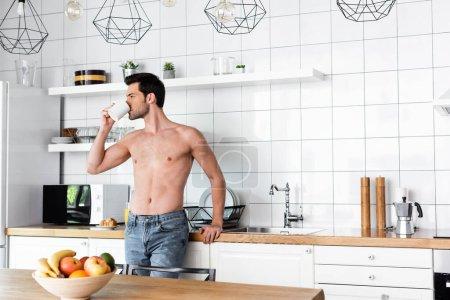 hombre guapo sin camisa beber café en la cocina por la mañana