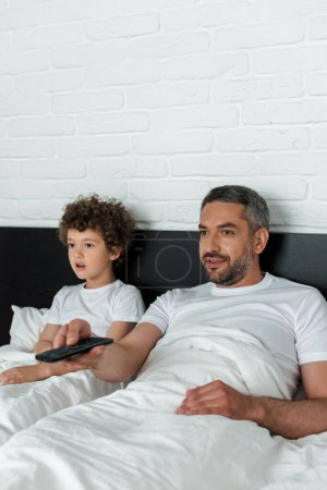 selective focus of bearded father holding remote controller near surprised son