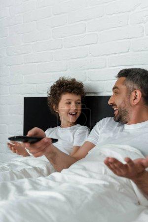 Photo pour Foyer sélectif de père joyeux tenant télécommande près garçon heureux - image libre de droit