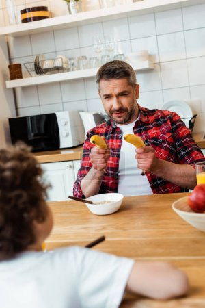 Photo for Selective focus of father holding fresh bananas while playing with curly son near breakfast on table - Royalty Free Image
