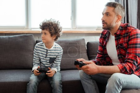 KYIV, UKRAINE - MAY 14, 2020: handsome father and curly son playing video game in living room