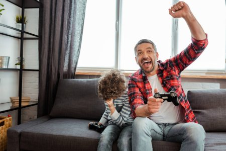 Photo for KYIV, UKRAINE - MAY 14, 2020: happy father celebrating triumph near curly son while holding gamepad in living room - Royalty Free Image