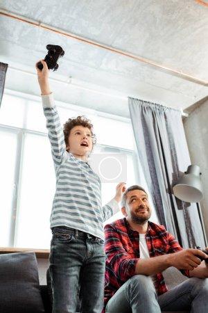 Photo pour KYIV, UKRAINE - 14 MAI 2020 : vue en angle bas du beau père regardant son fils excité célébrer le triomphe tout en jouant à un jeu vidéo - image libre de droit
