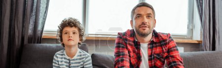 horizontal image of handsome father and cute son watching movie in living room
