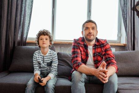 Photo pour Beau père et mignon fils regarder le film dans le salon - image libre de droit